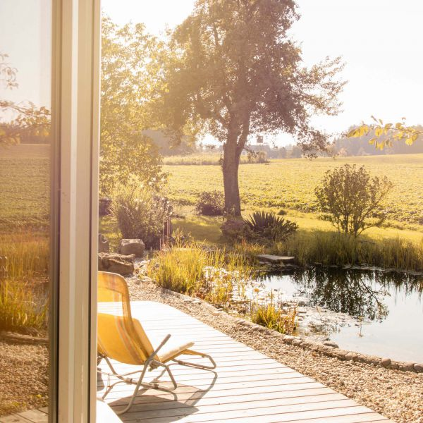 Das Bild zeigt die Sonnenterrasse hinterm Hof mit Blick auf den Teich.