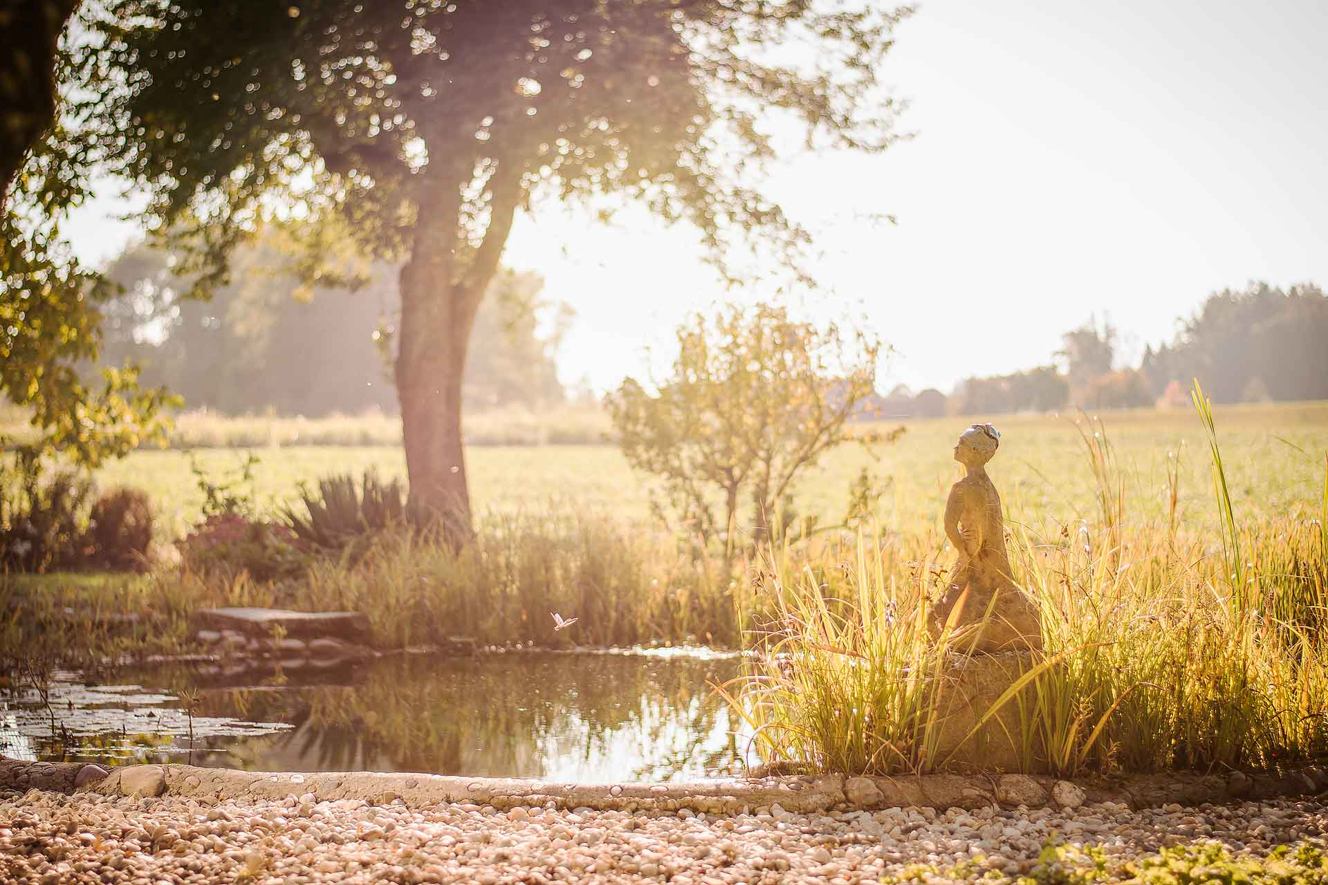 Das Bild zeigt eine von Muna modellierte Statue und im Hintergrund den Teich und den einen alten Baum.